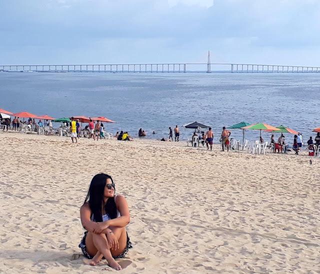 mulher de oculos escuros sentada na areia da praia