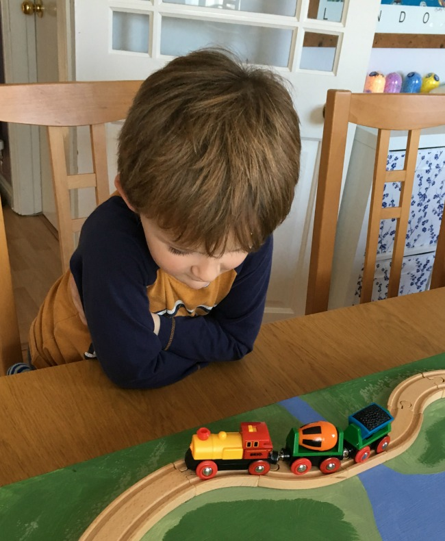 boy-watching-brio-battery-operated-action-train-chug-along-the-track