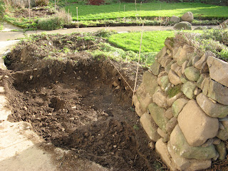 Completed wall end in the garden and the start of the excavation