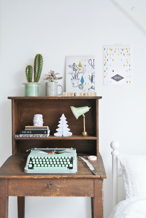 A wooden desk with a mint green typewriter, lamp, paper tree, a pile of books, a cactus and framed wall art above the desk against a crisp white wall