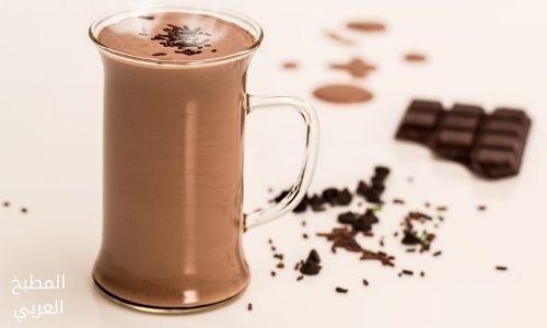 صورة مقربة لكوب زجاجي من الشوكولاتة الساخنة على طاولة مليئة بالشوكولاتة السوداء.