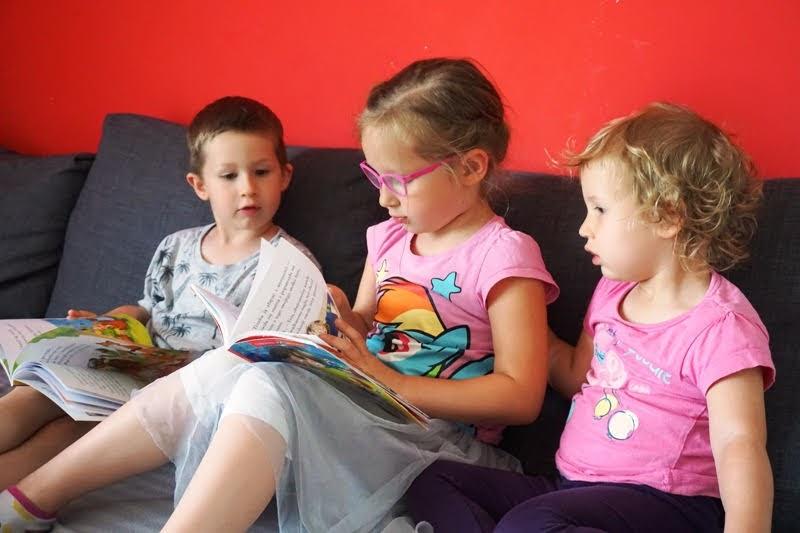 dzieci siedzące z ksiażkami