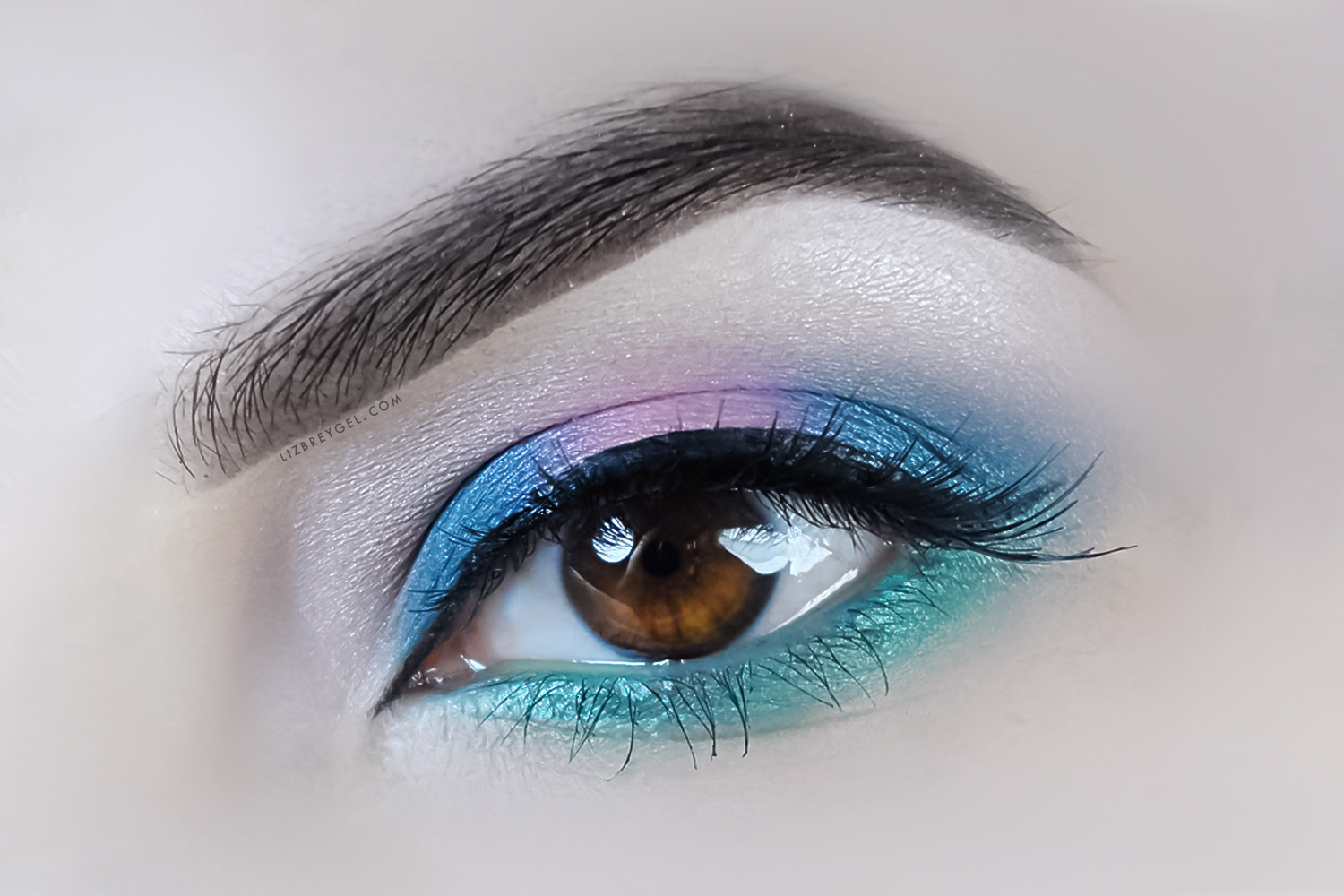 a close up picture of an eye with a colorful makeup look