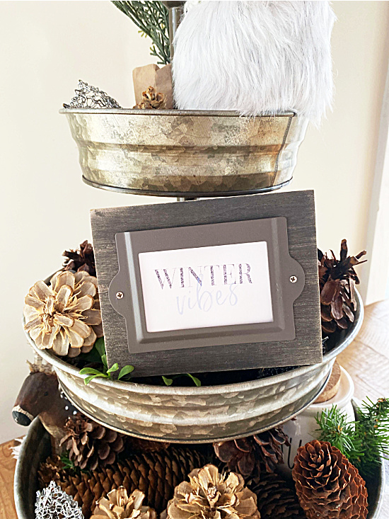 tray full of pinecones and a winter vibes sign