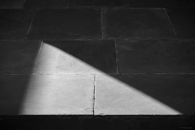 A Minimalist Photograph of a Right angled Light Triangle as seen on the floor at Jawahar Kala Kendra Jaipur, shot in black and white.