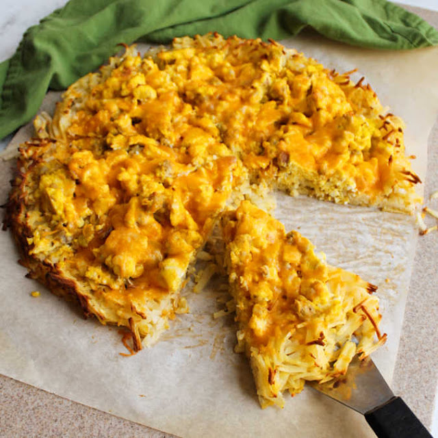 breakfast pizza with slice on spatula ready to serve and eat