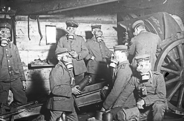 Gas attacks were a frequent menace in the Somme during the war so this group wear masks as they load shells into their gun in 1916.