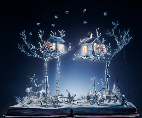 lighted altered book art paper sculpture showing trees, treehouses and a ladder