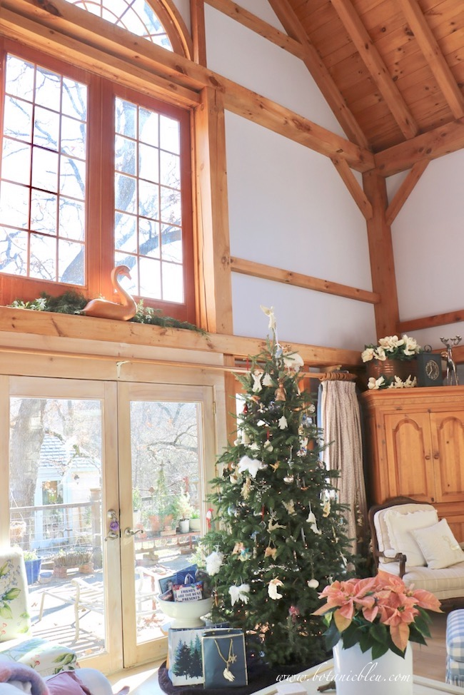 French country Christmas living room with Christmas tree in front of two story Palladian windows