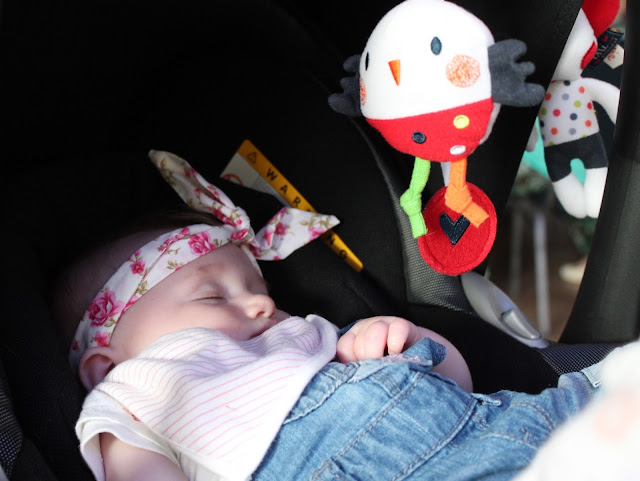 baby sleeping in pushchair wearing dungarees and floral wrap headband