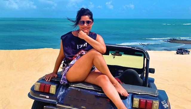 menina de cabelo preto e oculos escuros em dunas de areia