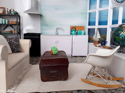 1/12 scale modern miniature scene of a kitchen and lounge in shades of white, teal, grey and light wood in a flat overlooking the sea.