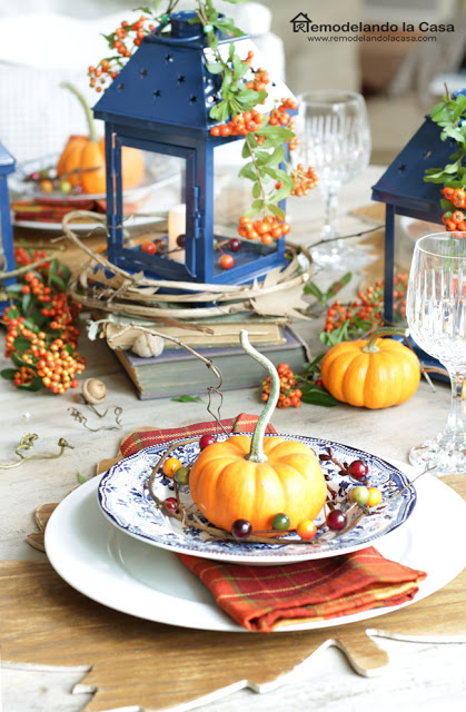 fall tablescape with blue plates and lanterns with orange pumpkins, napkins and beries