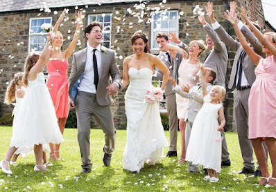 Guests throw peony petal confetti at wedding