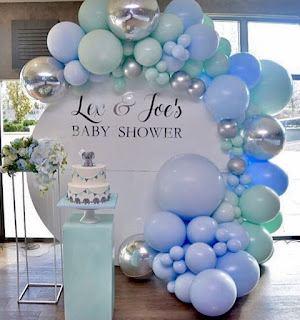 White round backdrop with organic balloon garland and cylinder stands for cake