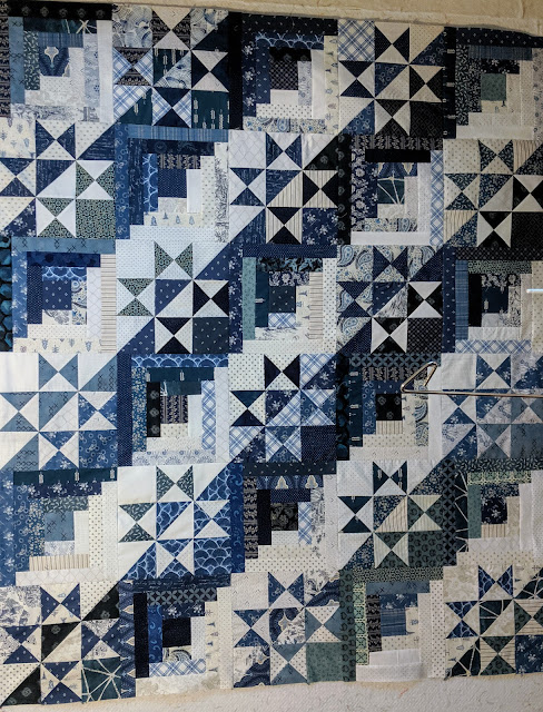 Alternating split Ohio Star and Log Cabin blocks in blue and white prints form this quilt top
