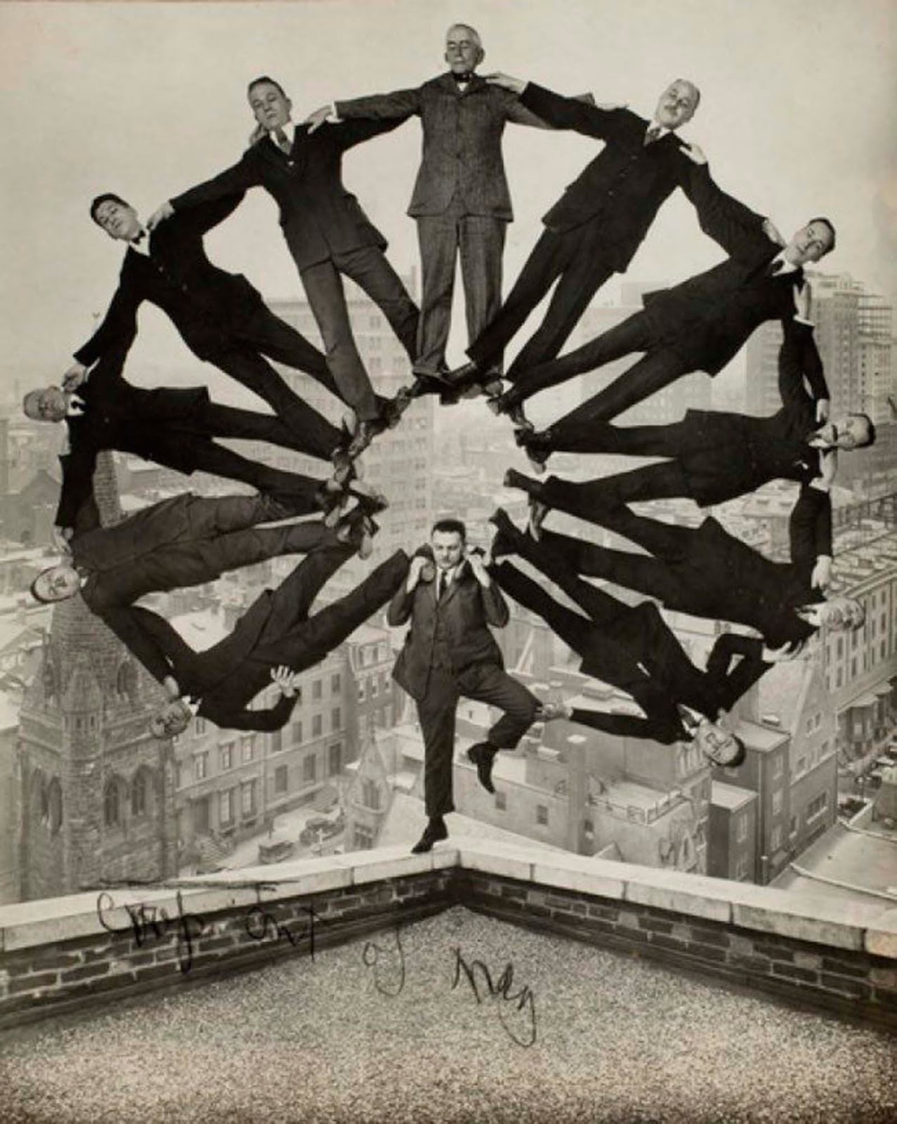 Man on rooftop with 11 men in formation on his shoulders. 1930.