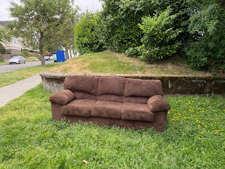 A brown couch on a green lawn in Seattle.