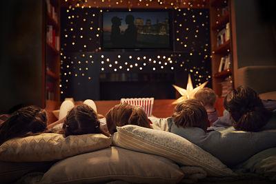 familia viendo película desde el sofá de su casa