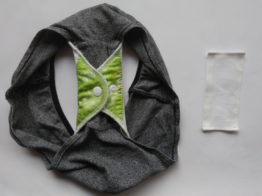 [Zdjęcie przedstawiające majtki z zapiętą podpaską oraz kawałek materiału w kształcie prostokąta]