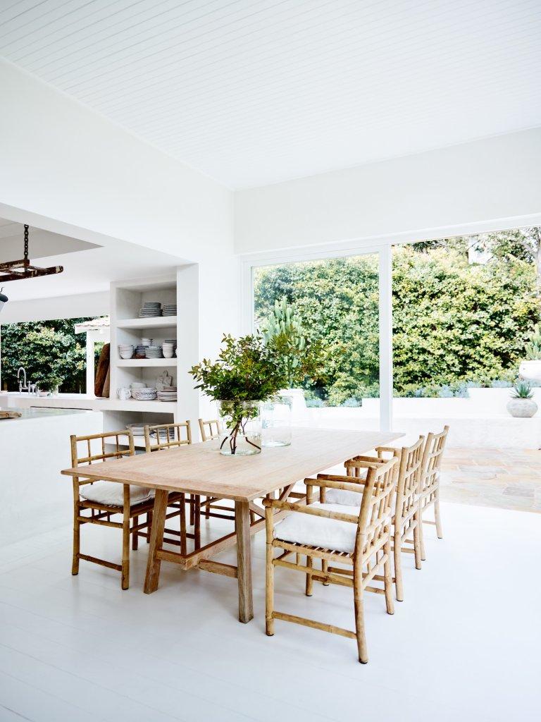 Cocina totalmente blanca y mesa de madera con sillas de mimbre y