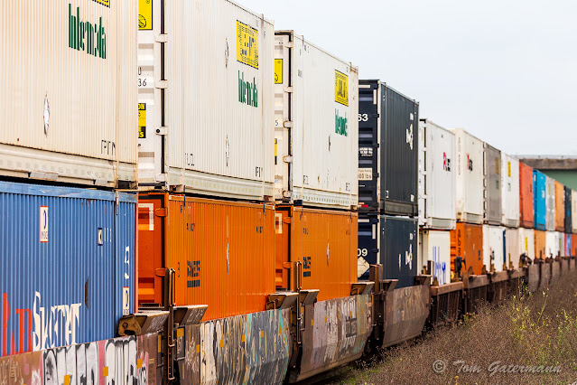 Double stack containers in well cars roll east at DeWitt Yard