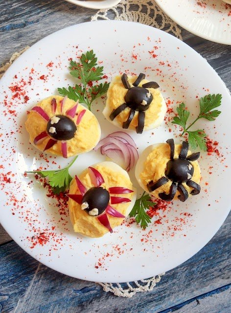 spider deviled eggs on a plate