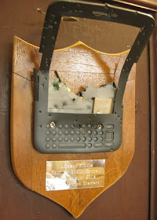 Destroyed Kindle mounted on a plaque. Brass plate reads: Amazon Kindle, Shot by Shaun Bythell, 22nd August 2014, Near Newton Stewart