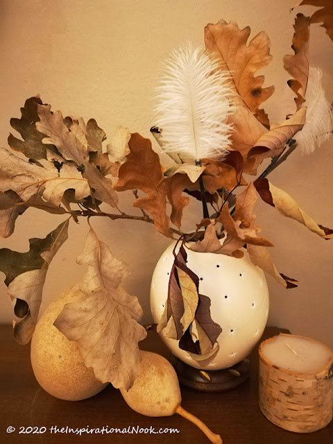 Dried botanical arrangment with ostrich feathers, oak leaves arranged in ostrich egg. Surrounded by a dried gourd and birch bark candle.
