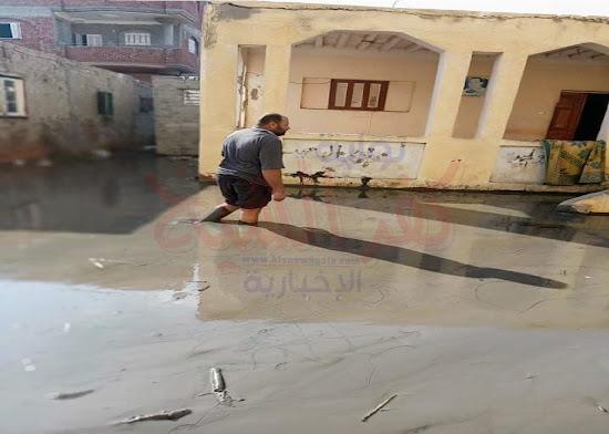 احد المواطنين خلال سيره في القرية وسط المياه