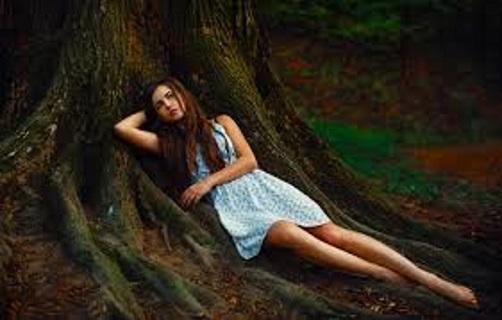 Uma jovem repousa pensativa num tronco de uma árvore centenária.
