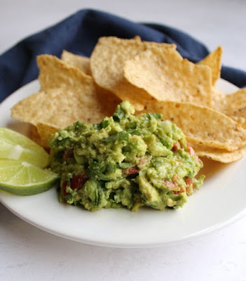 serving of homemade guacamole with chips and lime wedges