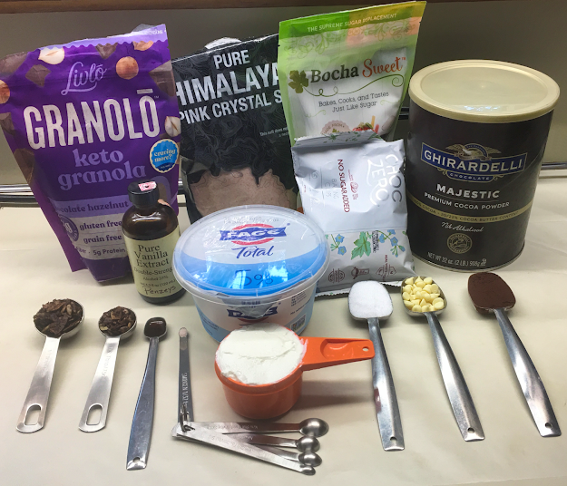 Photo of Livlo keto granola, pink Himalayan salt, Bocha Sweet sugar replacement, Ghirardelli Majestic Premium cocoa powder, Penzeys vanilla extract, ChocZero sugar free white chocolate chips, and Fage Total 5% Milkfat plain Greek yogurt