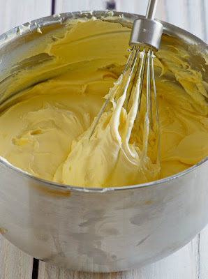 whisk in a bowl of pale yellow maple buttercream