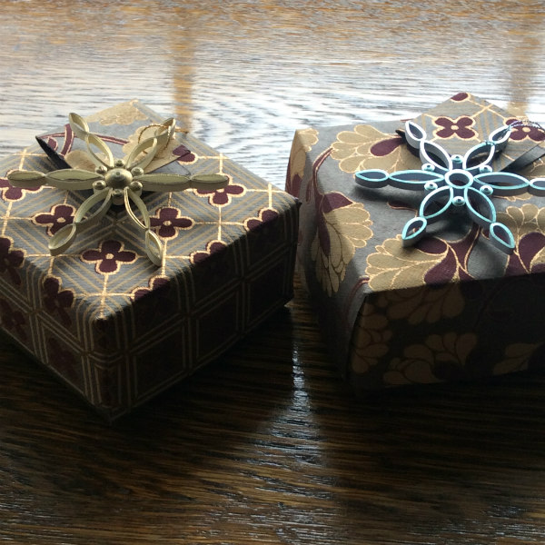 small handmade folded paper boxes with quilled snowflake gift toppers