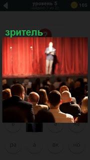 в зрительном зале сидят зрители и смотрят выступление артиста на сцене