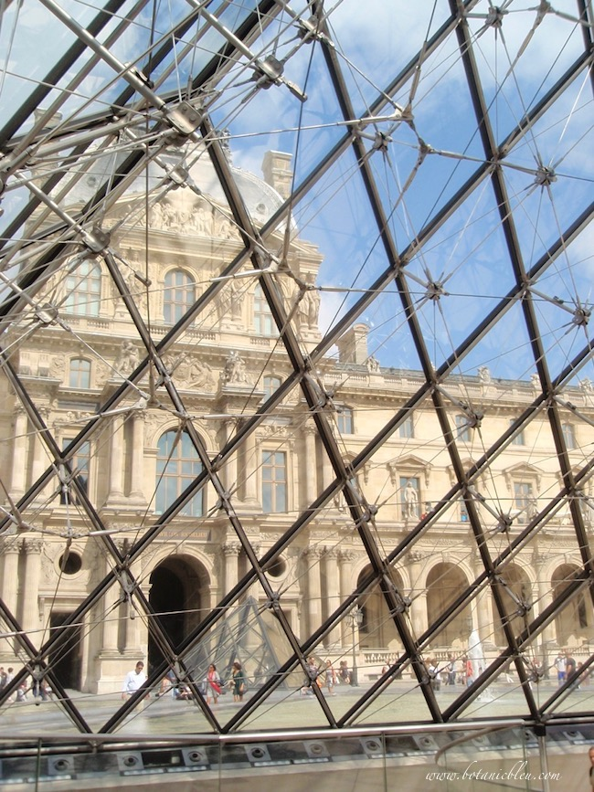 Classic French Renaissance Louvre seen through the main entrance glass pyramid