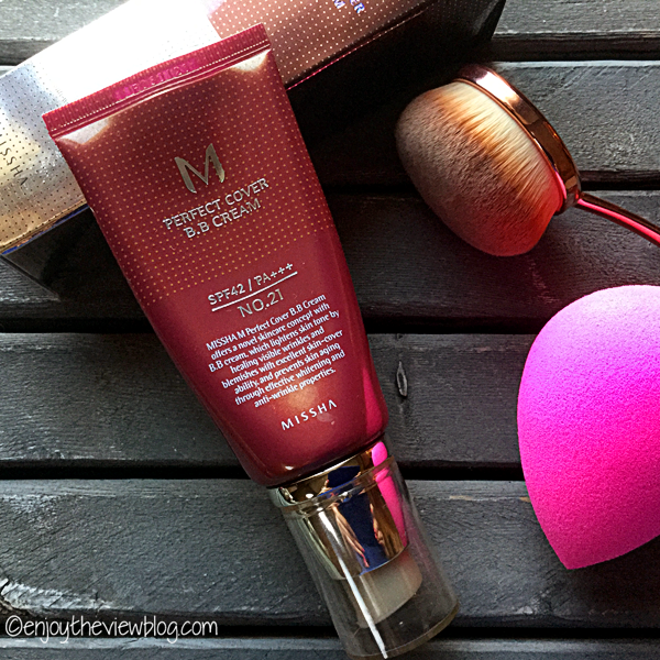tube of MIssha Perfect Cover BB Cream, beauty blender sponge, and paddle makeup brush
