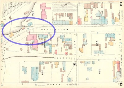 Ottawa fire insurance map 1878, plate number 43, with limits Sally (now Lyon, East), Queen (South), Concession (now Bronson, West) and Vittoria (one block north of Wellington, North). Scaled Outlines of buildings are drawn on the map, colour-coded to their construction (brick, wood, etc.), and information about water supply lines and hydrant locations. The broad roadway of Wellington Street sweeps from right to left two-thirds up the image, then near the left side of the image Wellington turns about 30 degrees to its left and narrows. I've put a blue ellipse to highlight this intersection, off of which a very narrow lane extends in line with Wellington Street where it quickly encounters, and apparently descends, a steep hill which cuts across the top-left corner of the image. The lane is shown dotted and it peters out before reaching the dotted lines showing the imagined northerly extension of Concession (Bronson).