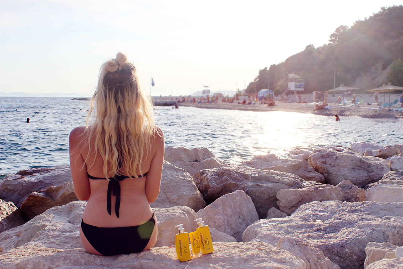 Blonde girl in Split at the beach with stay sun protection by beaute pacifique
