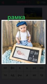 сидит ребенок и около его ног лежит рамка с фотографией и даты