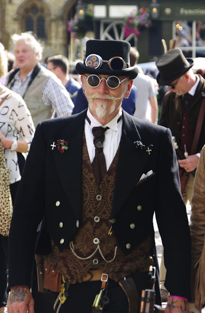 Steampunk man dressed in costume. his clothing includes waistcoat, hat, goggles, sunglasses, coat, tie, pin, belt and trousers.