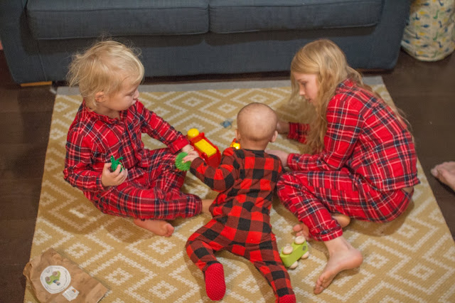 3 children in Christmas pyjamas playing with toys on Christmas morning