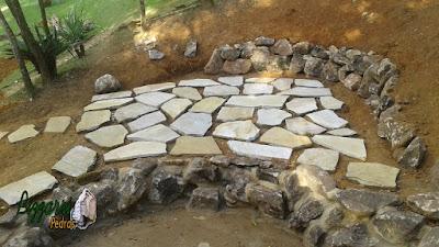 Execução do piso de pedra com junta de grama na execução da cascata de pedra com pedra moledo em sítio em Nazaré Paulista-SP.