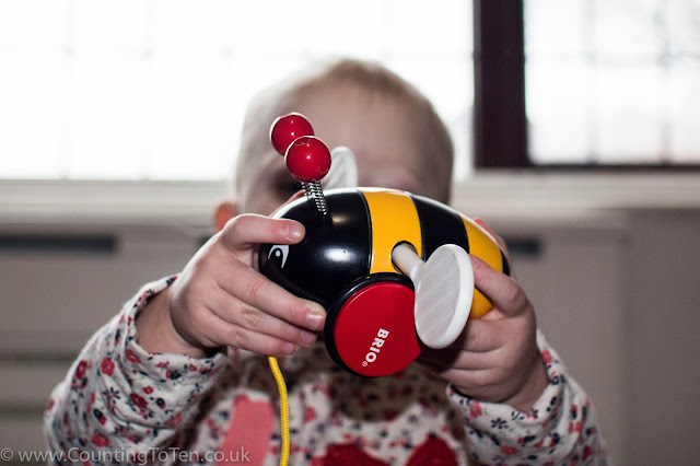 My toddler holding the Brio Pull Along Bumblebee in front of her face