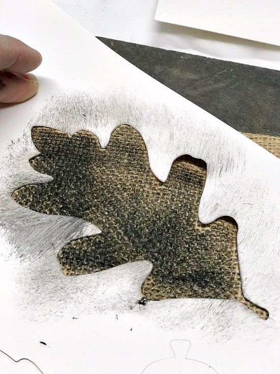 Stenciling an oak leaf with black paint