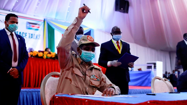Lieutenant general Mohamed Hamdan Dagalo of Sudan holds up a pen before signing a peace deal with rebel groups on August 31.