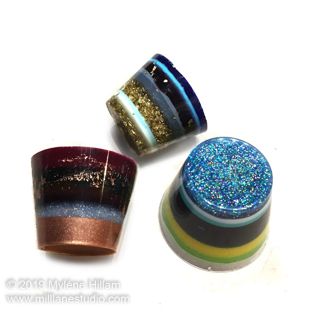 Three 1oz cups filled with multicoloured stripes of resin