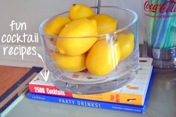 A cocktail recipe book and fresh lemons for garnishing.