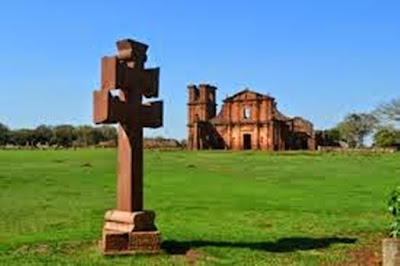 A foto mostra as ruínas de São Miguel das Missões, na frente a cruz missioneira e no fundo a Igreja em ruínas.